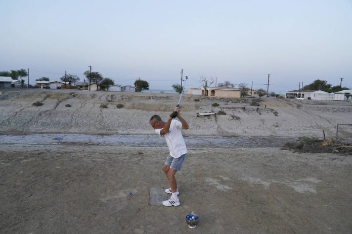 Greg Shank hits golf balls onto a dried up boating dock near his home in Salton City, Calif., Wedne...